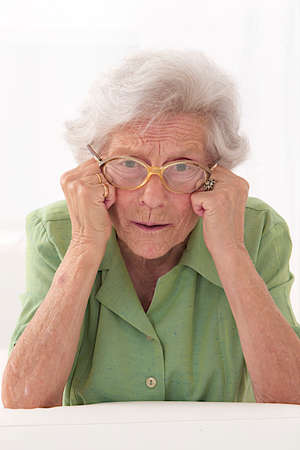 portrait of an unhappy senior lady with eyes glasses