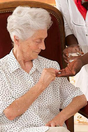 Home nurse giving elderly woman vitamin pills  photo