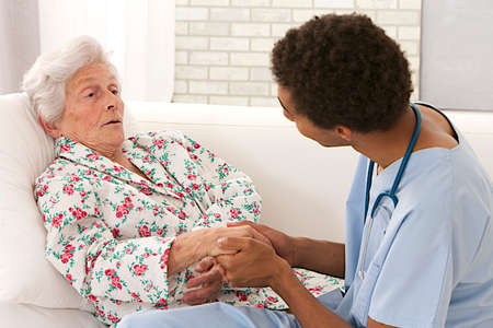 old age care: Young mulatto male doctor caring about a very old female patient