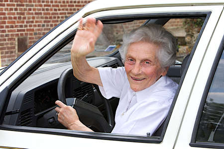 aging woman: Portrait of a smiling aging woman sitting in a vehicle  saying goodbye with her hand