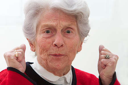 angriness: Closeup portrait of angry, furious elderly woman raising clenched hand Stock Photo