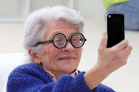 Happy elderly woman wearing funny eyesglasses selfie herself with her smart phone  photo