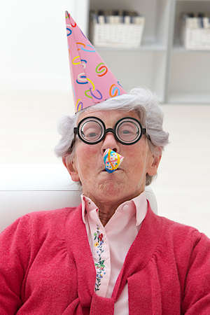 noise maker: happy mature woman with party hat and noise maker