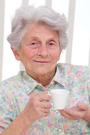 Senior woman enjoying cup of tea at home photo