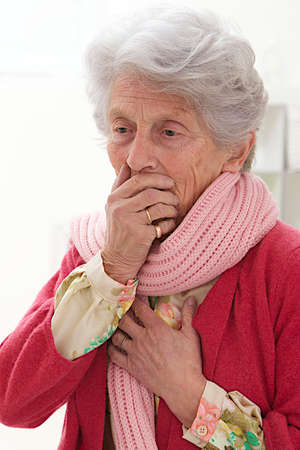 queasy: senior woman holds her hand to her mouth while feeling nauseous