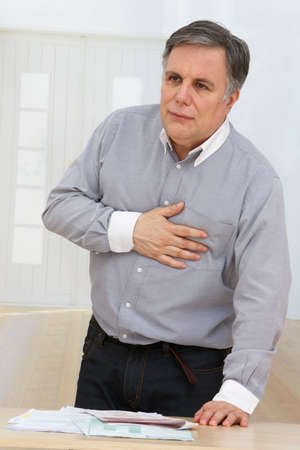 heart pain: A mature man having a heart pain in his living room, after racing financial paper Stock Photo