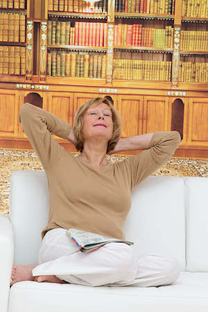 Happy woman relaxing in her sofa at home in front of bookshelves photo