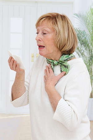hardly: Elderly woman has flu and sneezing hardly