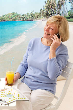 lap top: senior woman relaxing on the beach cafe using a cellular