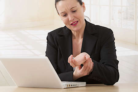 pinched: Woman with arthritis massaging hands in pain at office