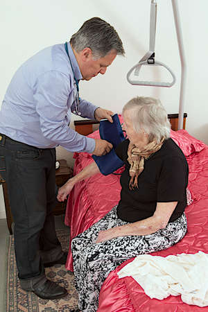 Male doctor taking the pulse of an older woman  photo