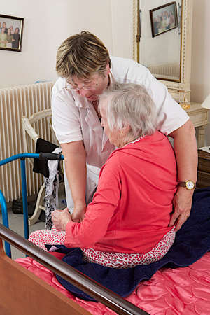 care giver: Care giver helping elderly woman to dress at home Stock Photo