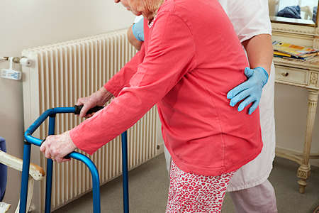 assisted living: Care giver helping elderly woman to walk with a walker