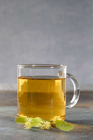 spasmodic: Cup of herbal tea with linden flowers on grey background