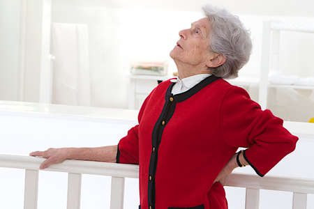 low back: Old woman holding her lower back. Low back pain