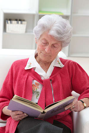 grey haired: Smiling Grey haired senior woman relaxing at home reading a book