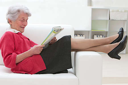 Smiling elderly woman reading on a sofa relaxing with feet over the arm couch photo