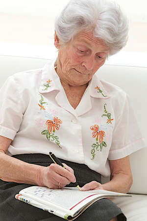 senior woman completing crossword  in a magazine  photo