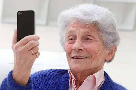 Happy elderly woman selfie herself with her smart phone  photo