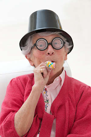 maker: happy mature woman with funny big eye-glasses , party hat and noise maker