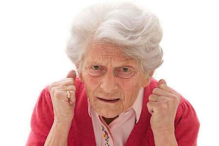 violent: Angry old woman making fists on white background
