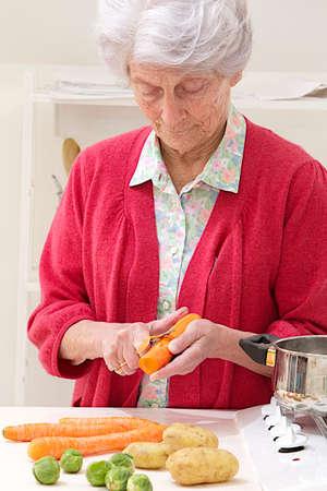 skinning: Senior women preparing vegetables,  she is focus on skinning   carrots