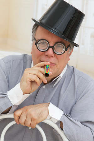 silliness: Senior man wearing party hat, and funny eyes glasses while blowing