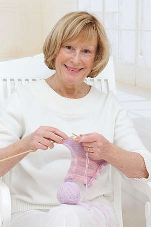 Portrait of senior woman knitting and looking at camera  photo