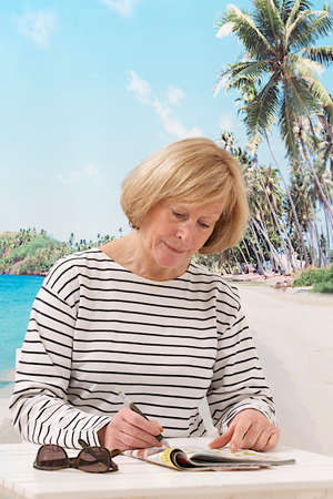 relaxed woman sitting on beach background concentrated on crossword in a magazine photo