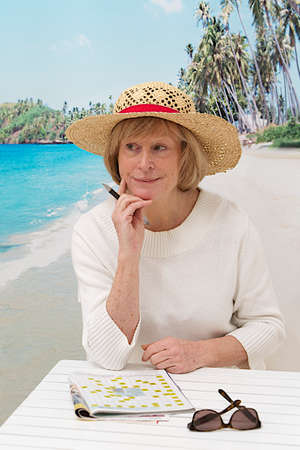 relaxed woman with hat  sitting on beach background doing crossword photo