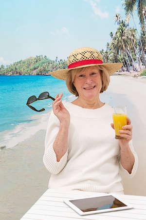 relaxed woman with hat  sitting on beach enjoying orange juice photo