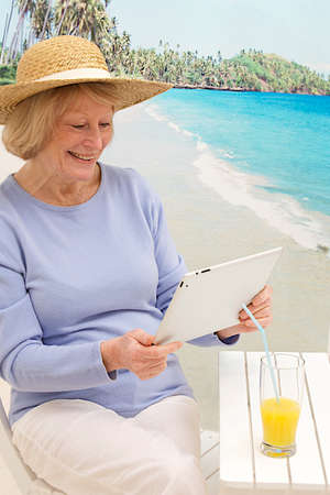 senior woman having fun with her tablet on the beach photo