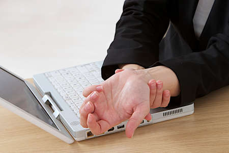 carpal tunnel: close up image of woman  with arthritis massaging hands in pain at office