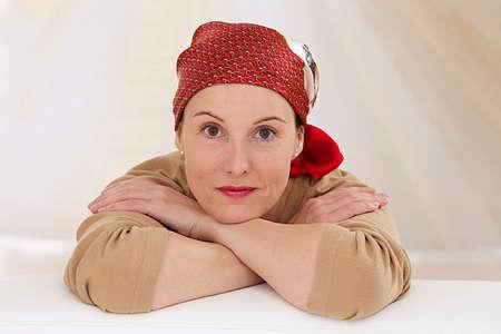 Portret van een mooie vrouw van middelbare leeftijd herstellende na chemotherapie - zich richten op haar lachende ontspannen houding