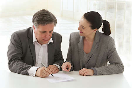 Image of business woman pointing document to business man  for signature  at the office photo