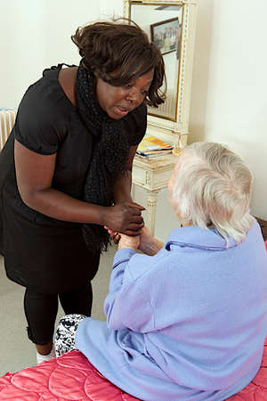 old carer: comfort and support from  care giver to elderly woman at home Stock Photo