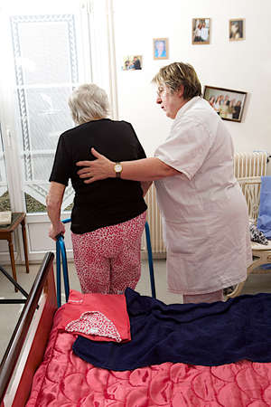 Care giver helping elderly woman to stand up with a walker
