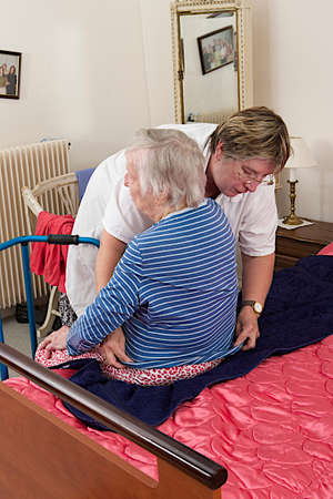 care giver: Care giver helping elderly woman to get dressed