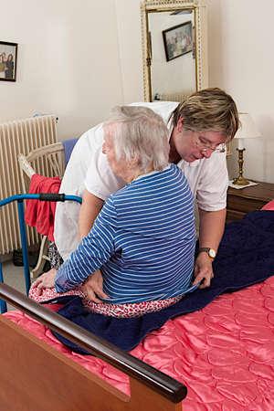 giver: Cuidador ayuda a la mujer de edad avanzada que se vistiera Foto de archivo