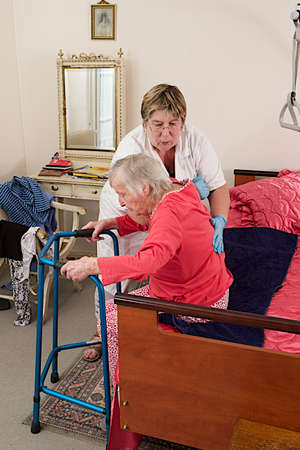 treating: Care giver helping elderly woman to stand up with a walker