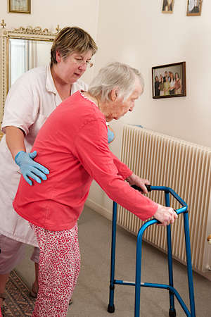 Care giver helping elderly woman to walk with a walker photo