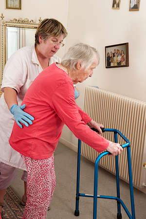 giver: Cuidador ayuda a la mujer de edad avanzada que caminar con un andador