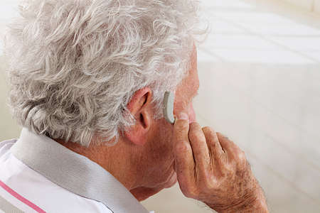 Close-up picture of a  senior man trying  Hearing Aid -Focus on the hearing aid.  photo