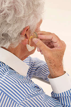 audible: Closeup of a senior  man inserting a hearing aid in her hear. Focus on the hearing aid. Stock Photo