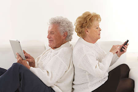 70 year old man: Senior couple seated back to back  playing with tablet and smartphone