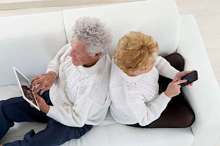70 year old man: top view of Senior couple seated back to back  playing with tablet and smartphone Stock Photo