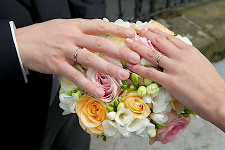 Bride and grooms hands with wedding rings lying down on a flowers bouquet  photo