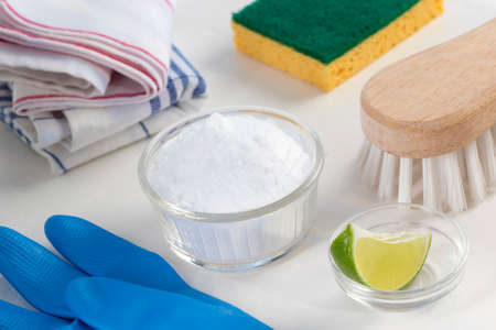 spring cleaning: Eco-friendly natural cleaners Vinegar, baking soda, salt, lemon and cloth on wooden table Homemade green cleaning