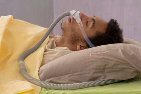 snoring: Man with sleep apnea using a CPAP machine