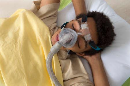 Man with sleep apnea using a CPAP machine photo